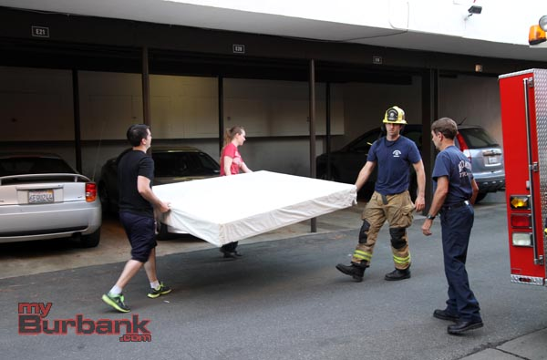 Burbank Fire Fighter Eric Rowley helps Jennifer & Konrad Lightner move the mattress, that they were carrying prior to saving a 3 year old who fell from a second story window. ( Photo by Ross A. Benson)