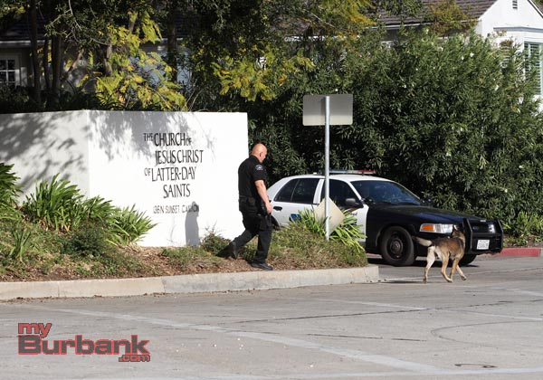 Burbank K-9 officer Joel Rodriguez with his dog Kimo look for possible evidence in the bushes near the parking lot of The Church of Later Day Saints, wher 2 males were stabbed Saturday afternoon.( Photo by Ross A. Benson)
