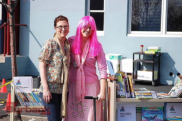 Washington Elementary Principal Brandi Young and Michelle Meta pose with scooter and carts of books for new breakfast reading program. (Photo By Lisa Paredes)
