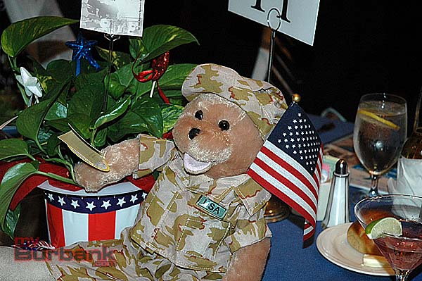 "Patriotic centerpieces at the Kiwanis Gala saluted Flag Day last Saturday and featured a bear dressed in USA military combat uniform waving the American flag. The bear plays Lee Greenwood's song ""I'm Proud to be an American"". ( photo by Joyce Rudolph)"