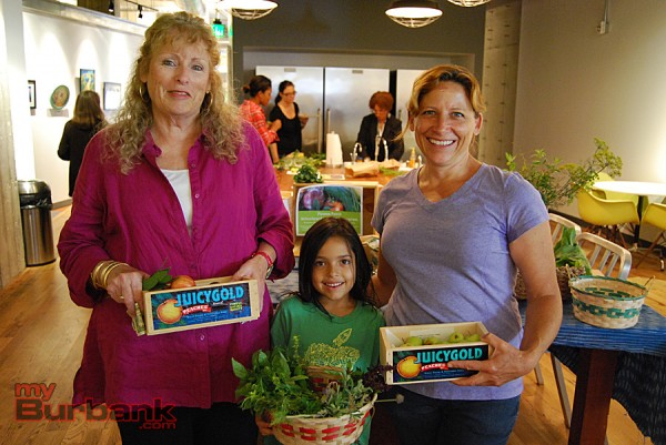 (from left to right) Zita LeFebvre from Cartoon Network, Stevenson second-grader Anya Kallianpur and Pirate Patch garden director Claire Torrey hold fresh produce and herbs. (Photo By Lisa Paredes)
