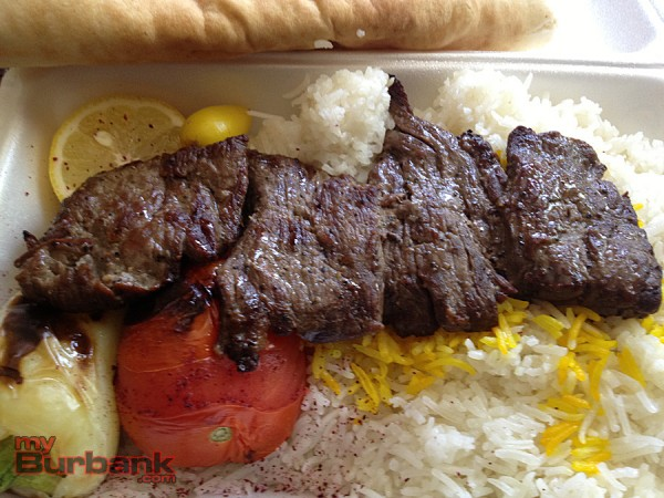 Shish Beef plate with tasty rice, grilled pepper, tomato and lemon, along with fresh pita. A side salad of cucumber and tomato and garlic butter spread are packaged separately for take out. (Photo By Lisa Paredes)