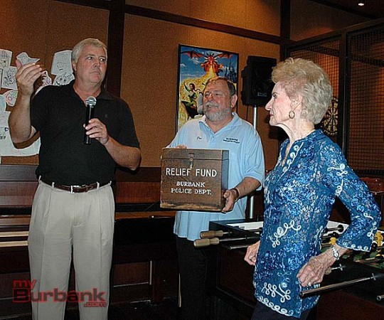 Story Tavern owner Ted Slaught, left, found an antique box that will be displayed in the original Tavern so that patrons can make donations to the Burbank Historical Society. Board member Don Baldaseroni holds the box while museum founder Mary Jane Strickland looks on. (Photo by Joyce Rudolph)