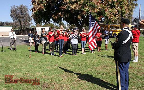 Burbank Mayor Dr. David Gordon (left) sings the national anthem as JBHS marching band plays and U.S. Army Sgt. Edmundo A. Bendana holds the flag. (Photo by Ross A. Benson)