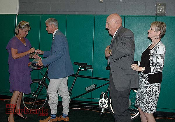 "Masters of ceremonies Michael Hastings, left, and Jack O'Neill change from their bicycle riding uniforms into their dinner attire with help from their assistants after arriving at the Family Service Agency's ""Imagine a City"" dinner on Saturday night at Providence High School gymnasium. (Photo by Joyce Rudolph)"