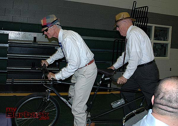 "Masters of ceremonies, Michael Hastings, left, and Jack O'Neill, make their grand entrance aboard a two-seater bicycle at the Family Service Agency ""Imagine a City"" dinner on Saturday night at Providence High School gymnasium. (Photo by Joyce Rudolph)"
