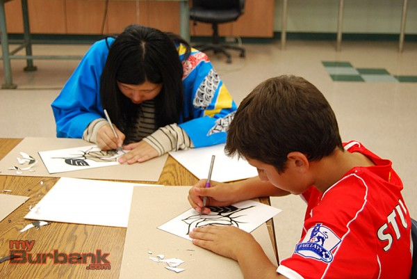 Rebun student Nagomi Sasamori joins students in Fatima Morales' art class for the art of Japanese paper cutting or Kyrie. (Photo By Lisa Paredes)