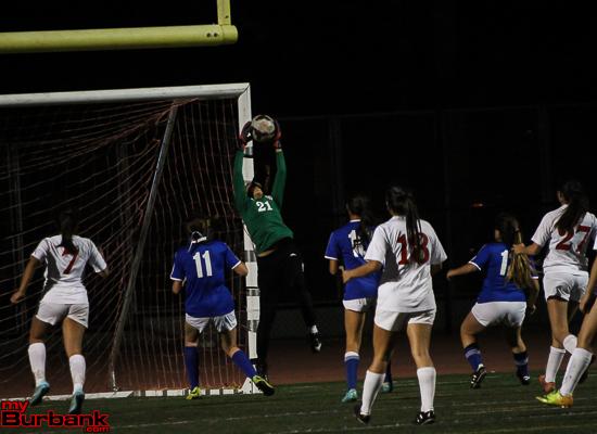 Burroughs goalie Emily Orsatt makes a sensational save in front of Burbank striker Kira Bochard, #11 (Photo by Ross A. Benson)
