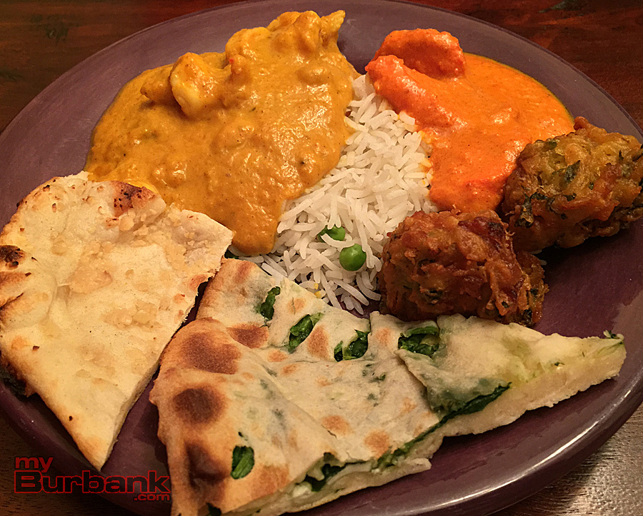 (clockwise from left) Garlic Naan, Shrimp Korma, Rice pilaf, Chicken Tikka Masala, Veggie Pakora and Spinach and Paneer Parantha from Gangadin Indian Cuisine provide a feast. (Photo By Lisa Paredes)