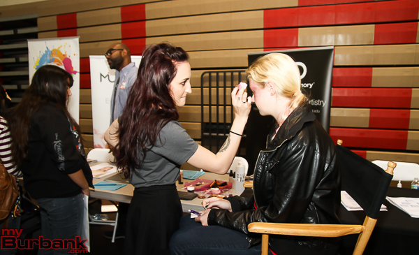 Dakota Sachs applies makeup to Carly King during career day at Burroughs. ( Photo by Ross A. Benson)