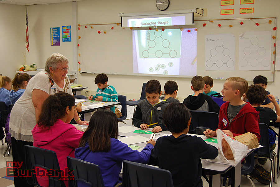Retired BUSD teacher Brenda Lister engages a group of fifth-graders working on the Fascinating Triangle puzzle. (Photo By Lisa Paredes)
