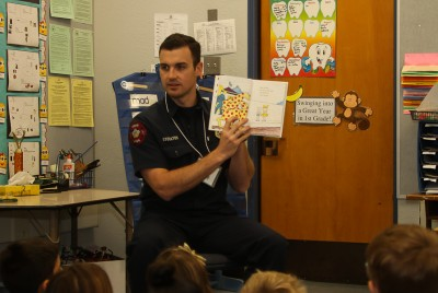 Burbank Fire Fighter Jon Stockton reads to a first grade class at Edison Elementary School. ( Photo by Ross A. Benson)