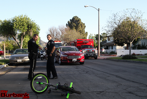 Burbank Police Officers Todd Burns and Angela Burrows investigate this auto 'vs' bicyclist on Thursday afternoon in the 900 block of Maple Street.  (Photo by Ross A. Benson)