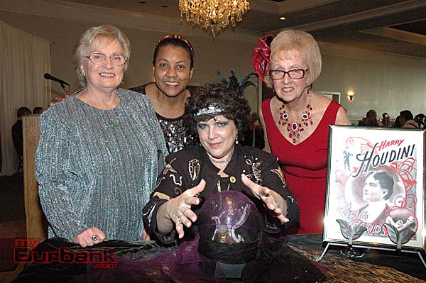 "Ann O'Donnell-Gardner, center, uses her crystal ball to channel Harry Houdini during La Providencia Guild's ""That Old Black Magic"" gala at the Castaway. She's surrounded by members, from left, Lorelei Kelley, Glenda Jones and Lynn White-Shelby."