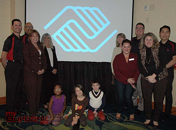 Marriott employees and Boys & Girls Club employees and members pose in front of the logo cast on the projection screen during the Thanksgiving dinner at the hotel.