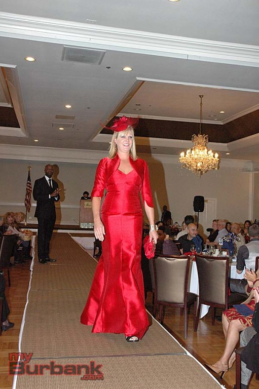 Erin Kurasz models a ruby evening gown from Holiday Hats and Gowns at the Patrons Club's fashion show. She was escorted by  Austin Kemie (in background). (Photos by Joyce Rudolph)