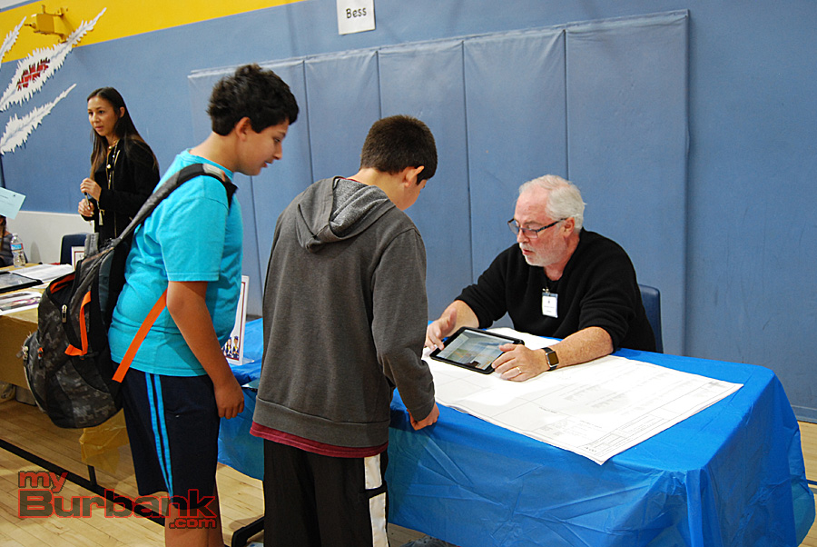 Two students investigate architect Van Hohlman's iPad demo. (Photo By Lisa Paredes)