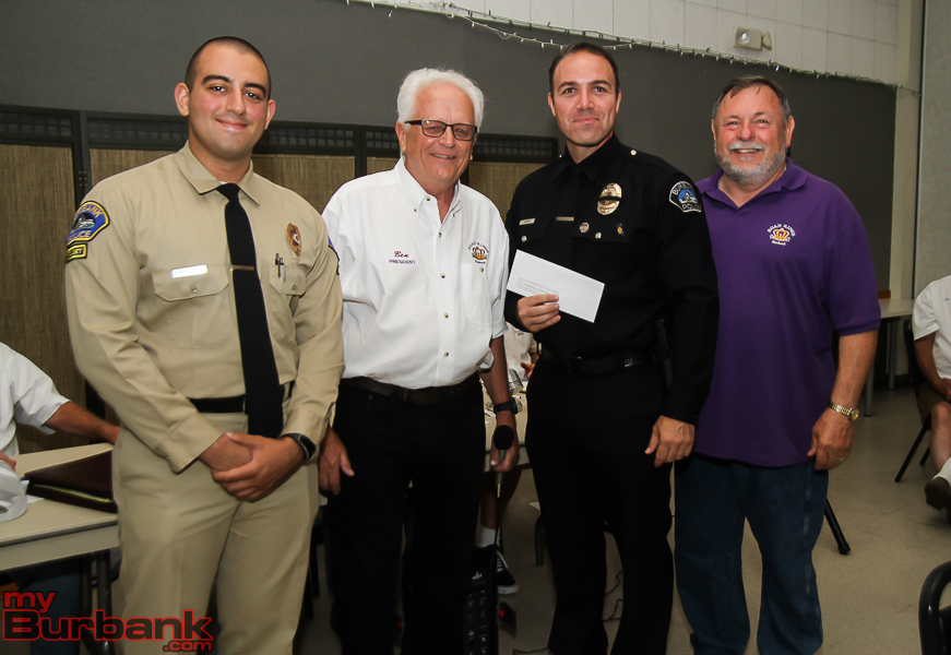 Burbank Police Officer Karel Castro accepts a check from Roads Kings for the Police Fire Museum. ( Photo by © Ross A. Benson)