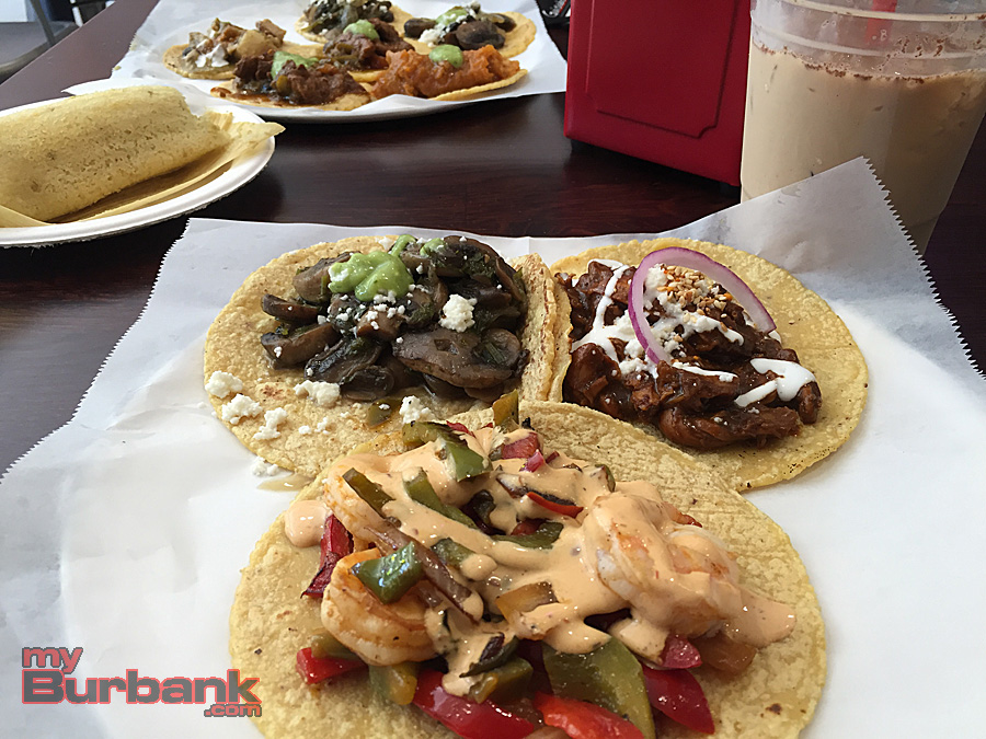 Trio of Guisados Burbank tacos: Camarones (front), Hongos con cilantro (left) and Mole Poblano (right), flanked by Horchata Coldbrew and a chicken tamale. (Photo By Lisa Paredes)