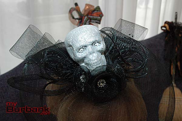 A detail photograph of La Providencia Guild President Lynn White-Shelby's fascinator headpiece featuring black netting and a faux skull.