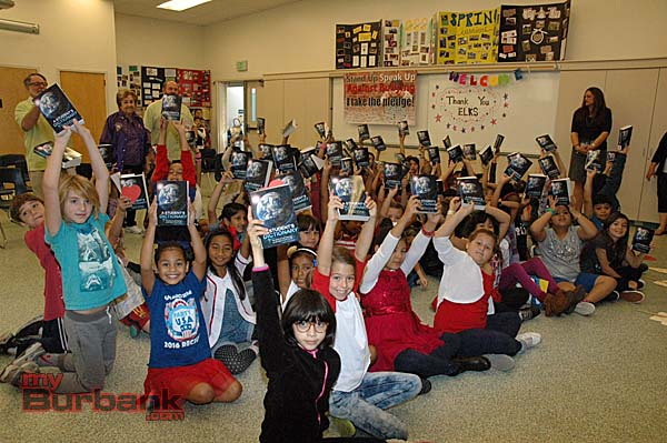 Three third-grade classes at Providencia Elementary School raise their dictionaries in jubilation after the donation presentation by the Burbank Elks Lodge. (Photos by Joyce Rudolph)